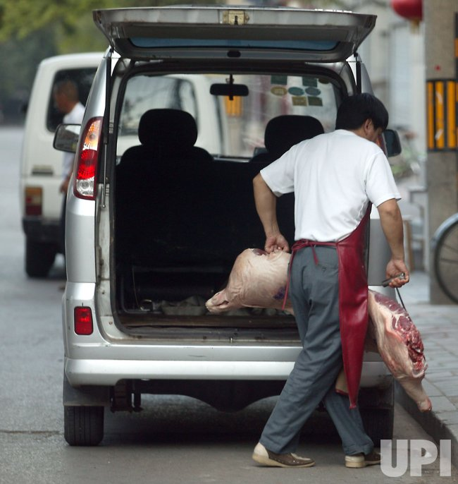 Man carries pig carcass in Beijing