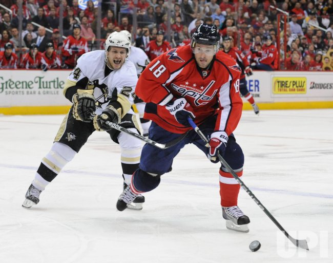 Capitals Belanger handles puck against Penguins Cooke in Washington
