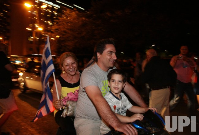 Greek citizens celebrate Antonis Samaras winning the largest vote in the Greek elections