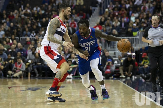 Los Angeles Clippers guard Patrick Beverley dribbles while defended by Washington Wizards guard Austin Rivers