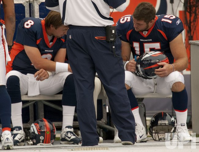 Broncos Orton and Tebow Look at Game Photos in Denver