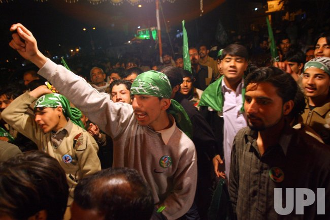 Pakistanis celebrate the unofficial results of Pakistan's general elections in Rawalpindi
