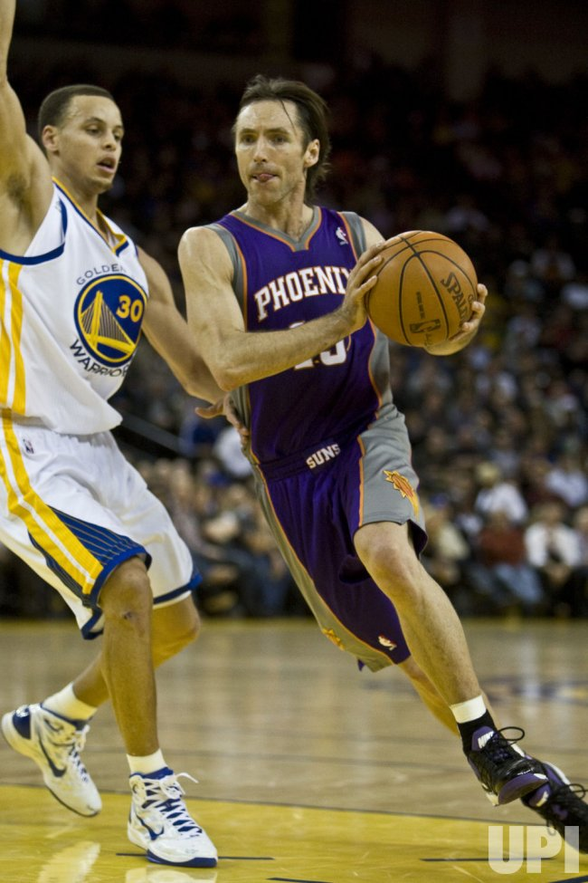 Phoenix Suns Steve Nash drives on Warriors Stephen Curry in Oakland, California