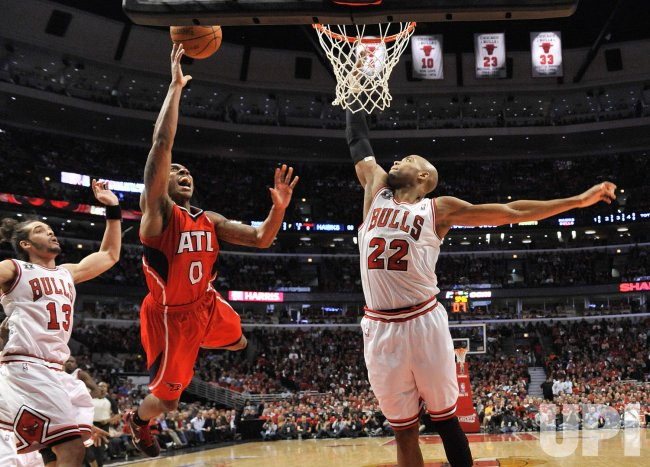 Hawks Teague drives past Bulls Noah and Gibson in Chicago