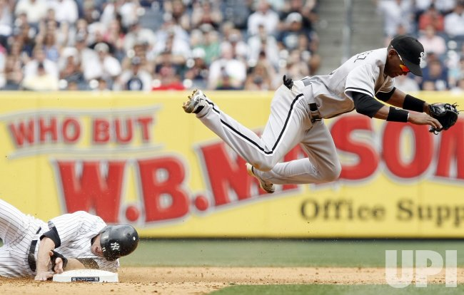 Chicago White Sox Alexei Ramirez leaps over New York Yankees Brett Gardner at Yankee Stadium in New York