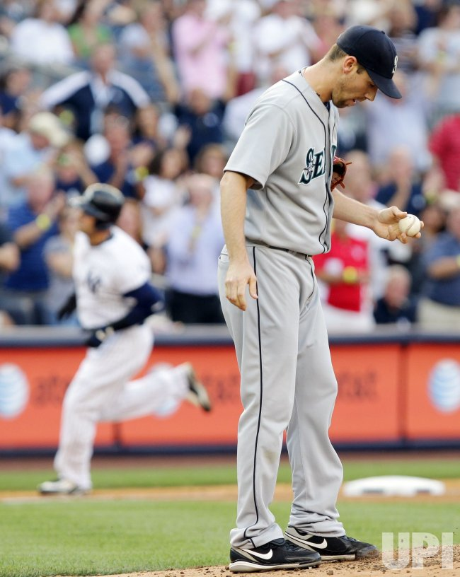 Seattle Mariners starting pitcher Cliff Lee reacts in the first inning as New York Yankees Nick Swisher runs the bases at Yankee Stadium in New York