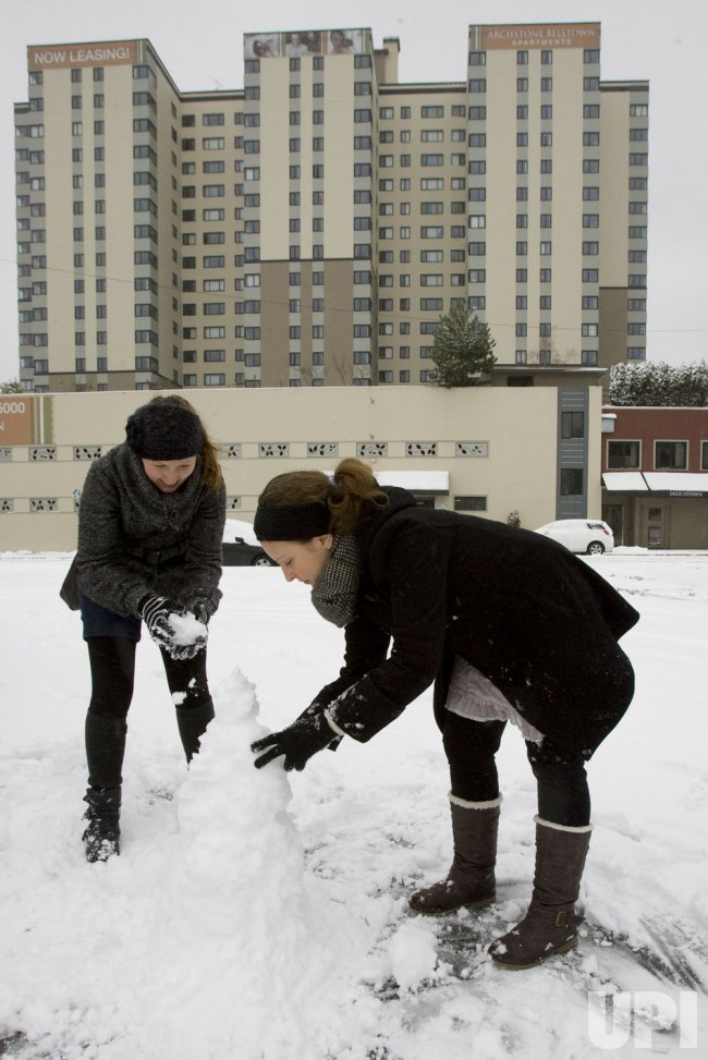 Seattle residents build a snowman after Seattle was blanketed with snow.