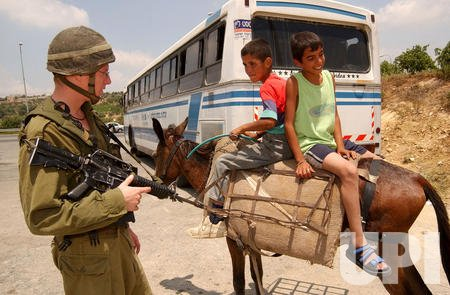 An Israeli soldier talks to Palestinian boys on a donkey at the Al Khader checkpoint near Bethlehem