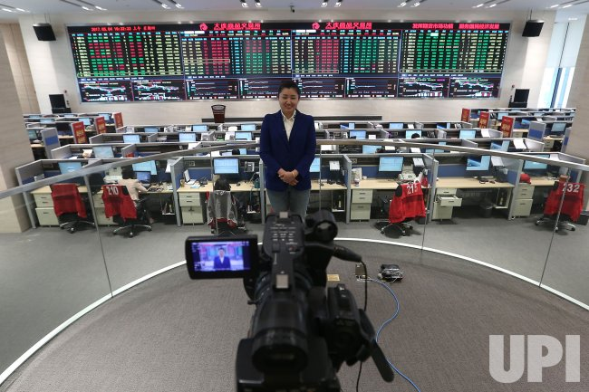 A Chinese financial analyst gives a 'live' TV update on trading in