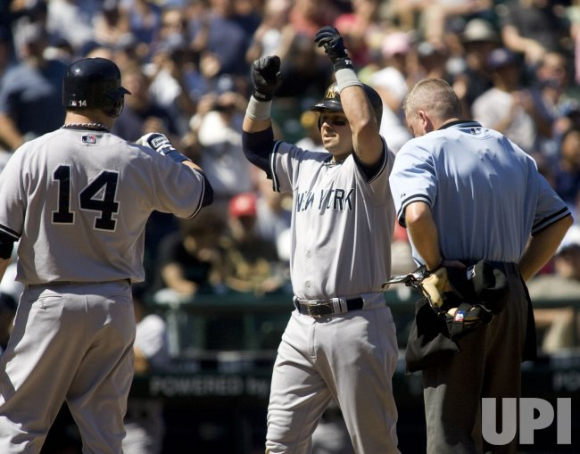 New York Yankees' Nick Swisher (R) is met at home plate by eric Hinslke after hitting a two run homer to center field against the Seattle Mariners in the fourth inning at SAFECO Field in Seattle.