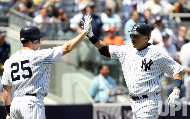 New York Yankees Nick Johnson and Mark Teixeira slap hands at Yankee Stadium in New York