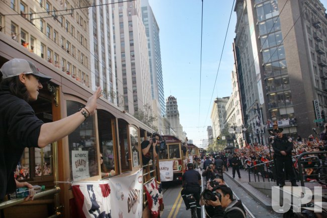 Giants ace Tim Lincecum waves from a motorized cable car in a massive parade for the world champions in San Francisco