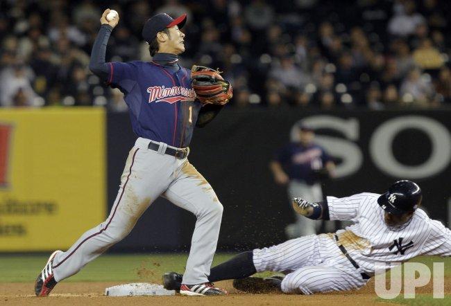 New York Yankees Curtis Granderson slides out into second as Minnesota Twins Tsuyoshi Nishioka at Yankee Stadium in New York