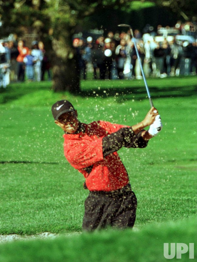 Tiger Woods blasts out of a sand trap on the second hole at Pebble Beach