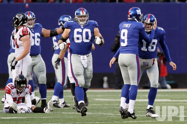 New York Giants Jeff Feagles (18) and Lawrence Tynes react after Tynes hits a 36 yard field goal in overtime to defeat the Atlanta Falcons in week 11 of the NFL season at Giants Stadium in East Rutherford, New Jersey