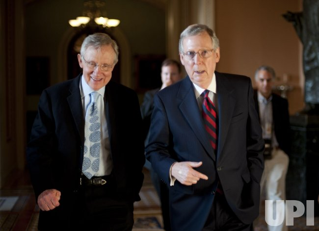 Senate Majority Leader Harry Reid and Senate Minority Leader Mitch McConnell walk together in Washington