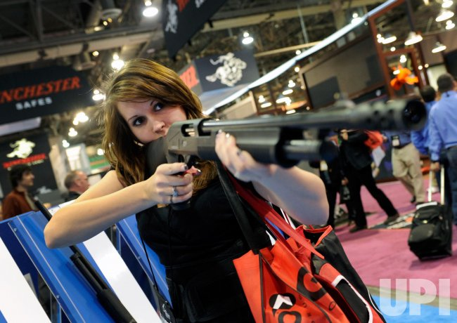 Lisa Deleon examines a shotgun at the 35th SHOT Show