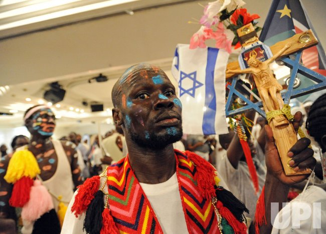 A Southern Sudanese refugee holds an Israeli flag and a crucifix during independence celebrations in Tel Aviv, Israel
