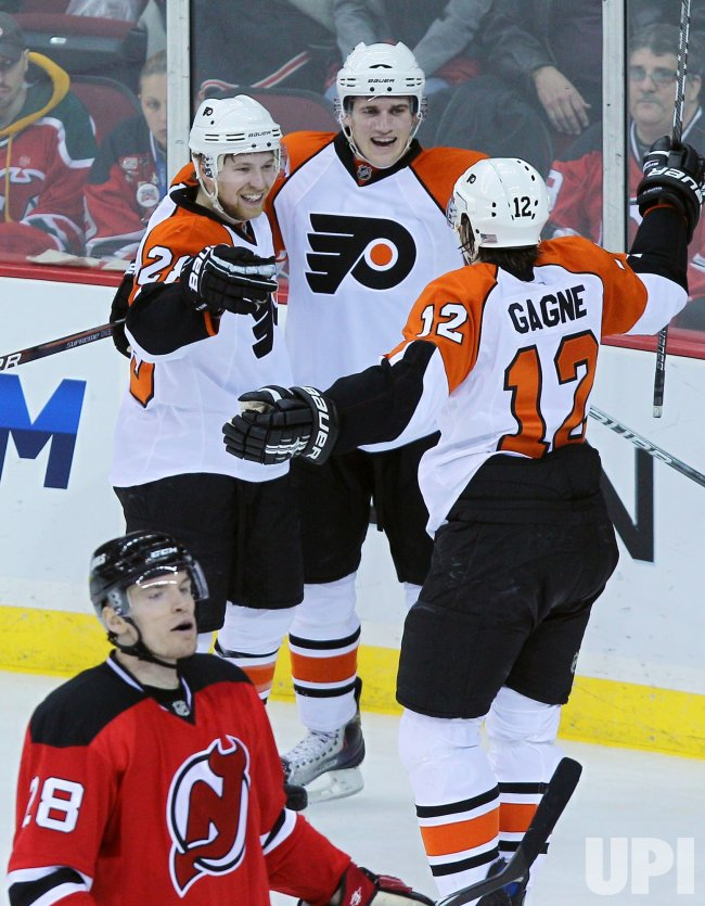 New Jersey Devils Martin Skoula stands near Philadelphia Flyers Claude Giroux (28) and Simone Gagne at Prudential Center in New Jersey
