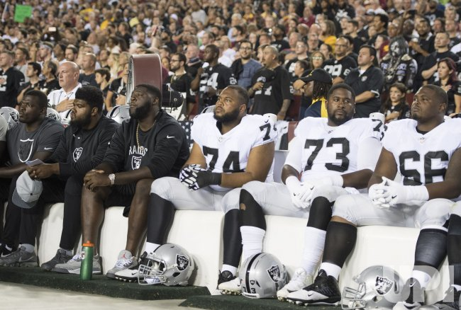 Members of the Oakland Raiders protest during the National Anthem