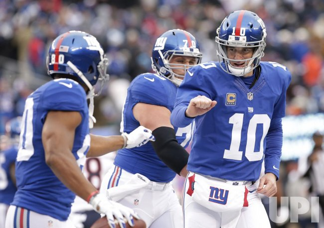 Giants Eli Manning celebrates with Victor Cruz