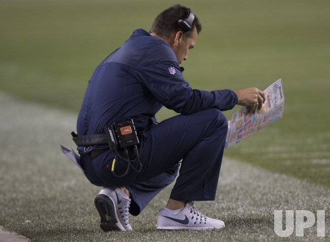 Broncos head coach Kubiak studies play chart in Denver