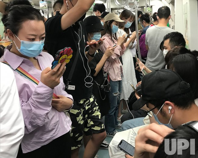 Commuters Wear Protective Masks On a Subway in Beijing, China