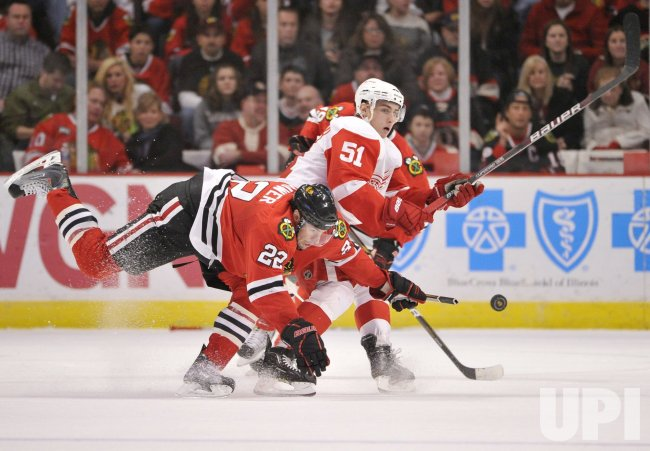 Red Wings Filppula knocks puck away from Blackhawks Brouwer in Chicago
