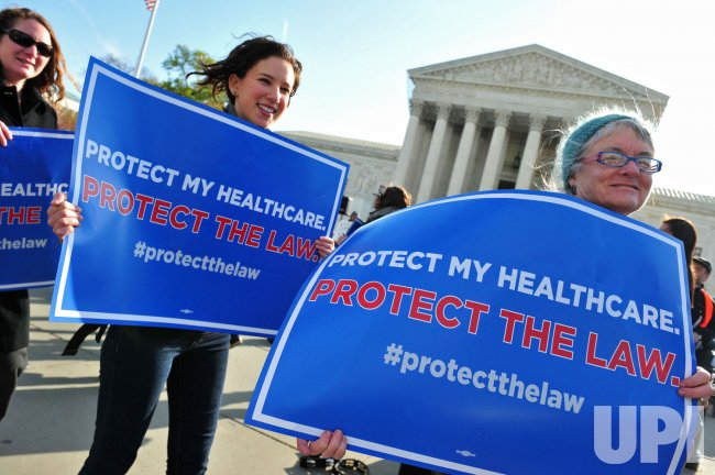 Protesters gather in front of the U.S. Supreme Court for the health care case in Washington