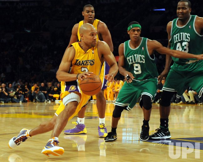 Lakers'Derek Fisher drives to the basket by Celtic's Rondo and Perkins during NBA game in Los Angeles