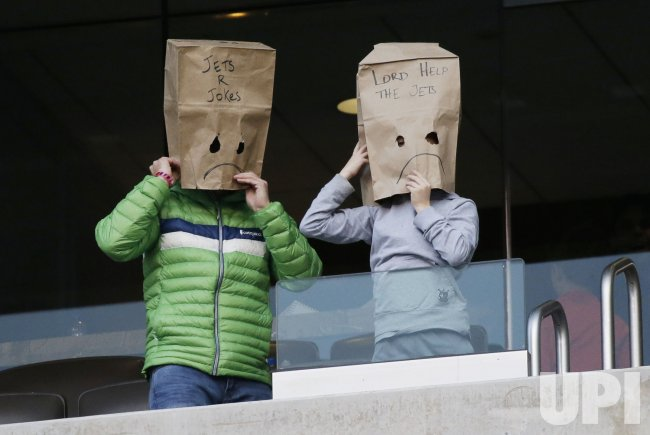 New York Jets fans hold paper bags on their heads