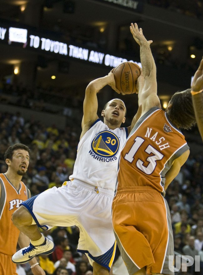 Warriors Stephen Curry takes a fade away against Phoenix Suns Steve Nash in Oakland, California