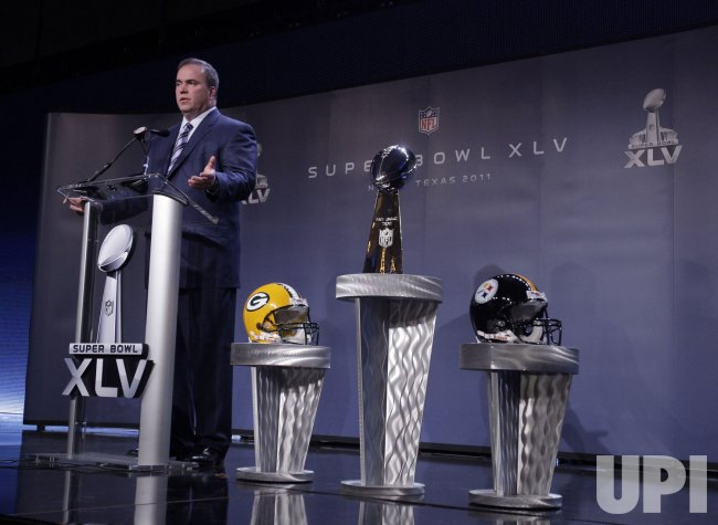 Green Bay Packers Head Coach Mike McCarthy stands next to the Vince Lombardi Trophy at a Press Conference in Dallas