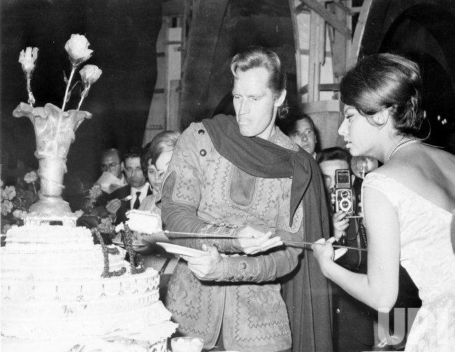 Charlton Heston cuts cake with Sophia Loren to celebrate the movie El Cid (Le Cid)