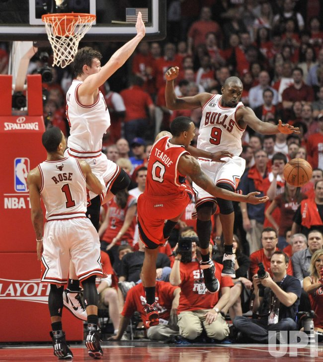Hawks Teague passes as Bulls Rose, Asik and Deng defend in Chicago