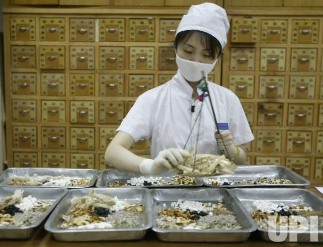 Workers prepare herbal medicines at Traditional Chinese Medicine Hospital in Beijing