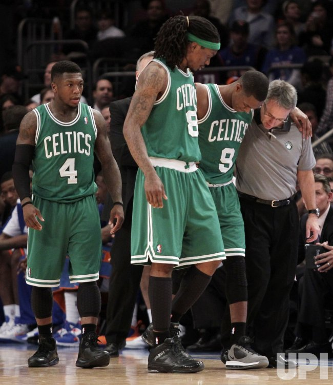 Boston Celtics Nate Robinson and Marquis Daniels help Rajon Rondo off of the court at Madison Square Garden in New York