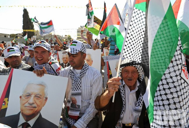 Palestinians hold posters of Palestinian President Mahmoud Abbas at a rally to support Fatah and commemorate the sixth anniversary of Yasser Arafat's death