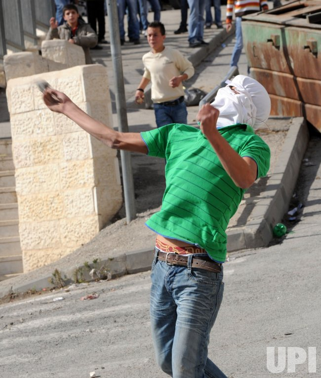 A Palestinian youth throws stones at Israeli forces