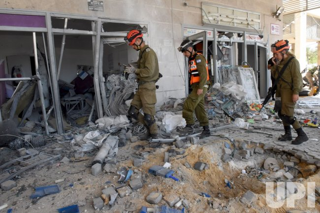 Israeli Soldiers Look At A Building Hit By A Rocket Fired From Gaza