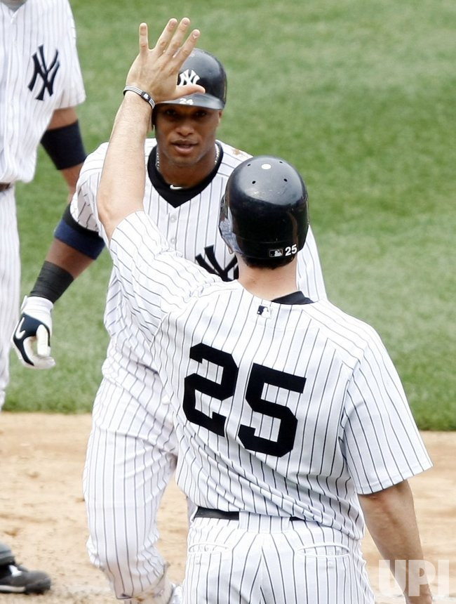 New York Yankees Mark Teixeira (25) raises his hand as Robinson Cano crosses the plate at Yankee Stadium in New York