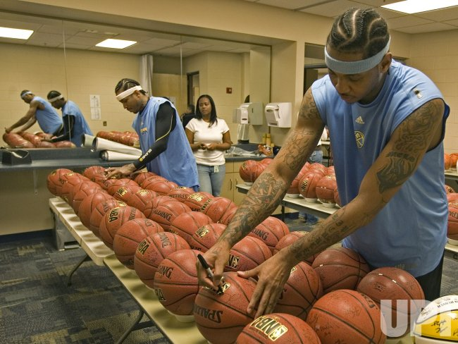 Nuggets Iverson and Anthony Sign Basketballs after practice
