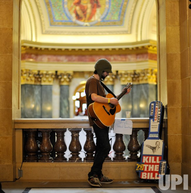 Fransee plays guitar in capitol in Madison, Wisconsin