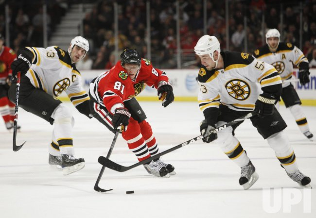 Bruins Chara, Morris and Blackhawks Hossa go for puck in Chicago