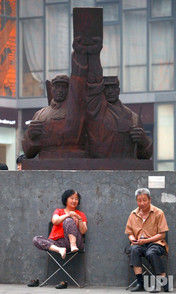 Two Chinese senior citizens sit under a patriotic statue in Beijing