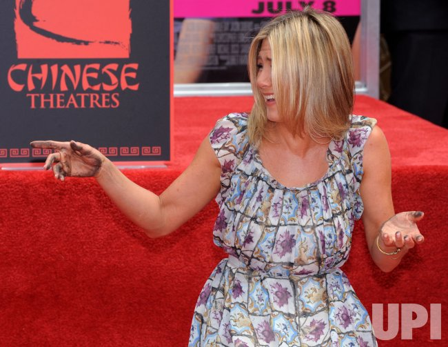 Jennifer Aniston points to fans during a ceremony at Grauman's in Los Angeles
