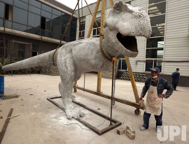 A Chinese employee works on the mold of a dinosaur in Zigong, China