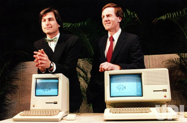 Apple Computer Company's Chairman Steve Jobs (L) and President John Sculley (R) display new computer hardware.