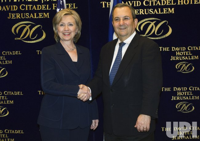 U.S. Secretary of State Clinton shakes hands with Israel's Defence Minister Barak in Jerusalem