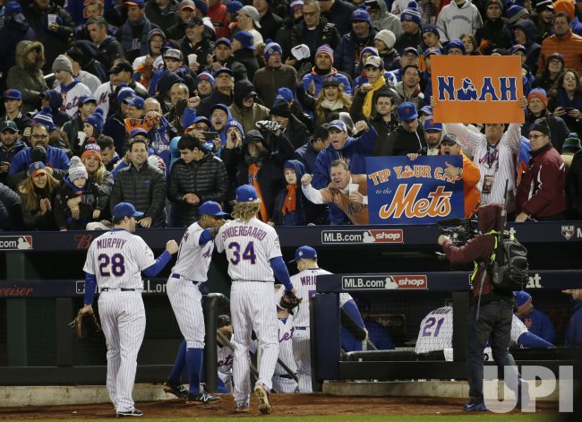 Fans react and hold up signs when New York Mets walk to dug out